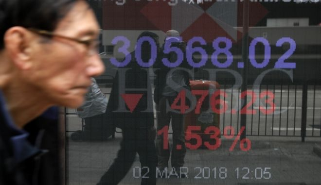 A man walks past an electronic board showing Hong Kong share index outside a local bank in Hong Kong, Friday, March 2, 2018. Asian shares posted steep declines Friday, adding to global stock market losses after President Donald Trump vowed to impose stiff steel and aluminum tariffs, sparking fears of a trade war. (AP Photo/Vincent Yu)