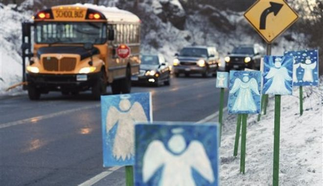 FILE - In this Jan. 3, 2013 file photo, a bus traveling from Newtown to Monroe, Conn., stops in front of 26 angels along the roadside on the first day of classes for Sandy Hook Elementary School students since the Dec. 14, 2012 shooting. Chalk Hill School in Monroe was overhauled so Sandy Hook students could be relocated to a different building after the shooting on Dec. 14, 2012, where 26 were gunned down inside the school building in Newtown. (AP Photo/Jessica Hill, File)