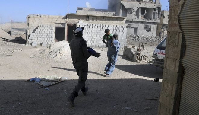 This photo released by the Syrian Civil Defense White Helmets, which has been authenticated based on its contents and other AP reporting, shows a member of the Syrian Civil Defense group carrying a victim after airstrikes and shelling hit in Ghouta, a suburb of Damascus, Syria, Wednesday, March. 7, 2018. Government forces carried out punishing airstrikes against an opposition-held suburb of Damascus, seeking to divide the besieged enclave in two and further squeeze rebels and tens of thousands of civilians trapped inside, state-run media and opposition activists reported. (Syrian Civil Defense White Helmets via AP)