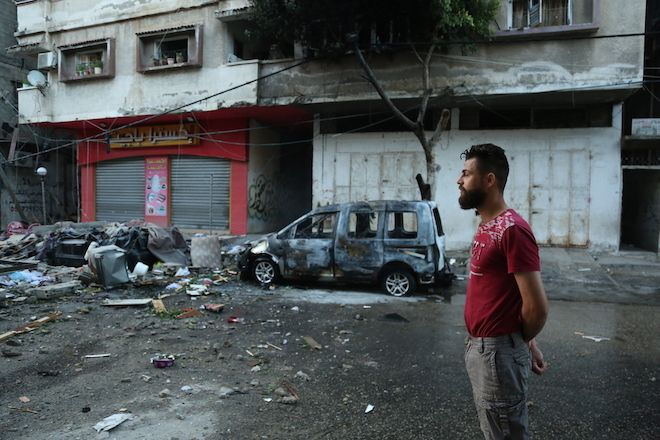 Palestinian man stands on the street of Gaza city after the night of heavy aerial bombardment. 11 days of Israels intense aerial and ground bombardments has caused a huge impact on peoples lives in Gaza - people lost their family members, their homes and livelihoods and have suffered long-lasting physical and psychological injuries.
