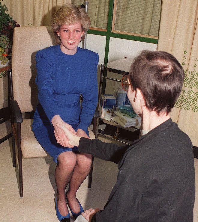 Η πριγκίπισσα Ντιάνα, σε χειραψία με έναν 32χρονο ασθενή με AIDS στο ιδιωτικό του δωμάτιο στο Νοσοκομείο Middlesex του Λονδίνου, 19 Απριλίου 1987. Ζητήθηκε από τον φωτογράφο να μην φωτογραφίσει το πρόσωπο του ασθενούς.