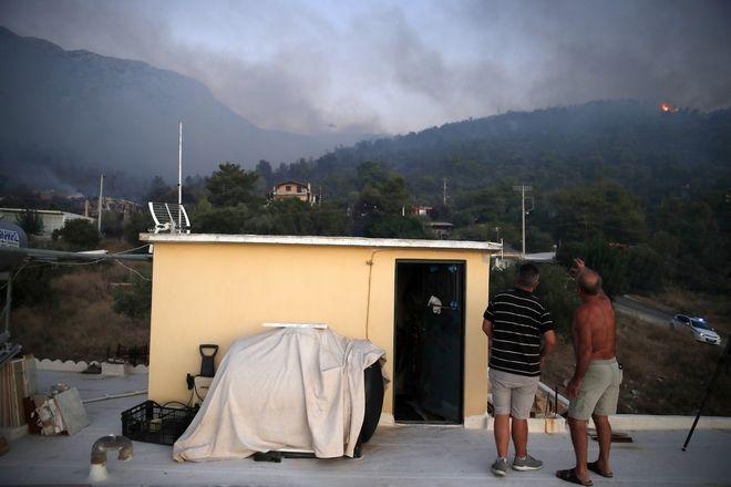 Κάτοικοι παρακολουθούν τη φωτιά στην Παιανία