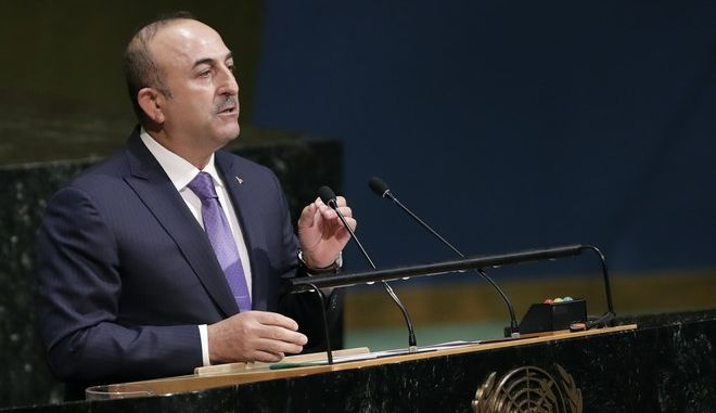 Mevlut Cavusoglu, right, Turkey's foreign minister, speaks at the General Assembly, Thursday, Dec. 21, 2017, at United Nations headquarters. President Donald Trump's threat to cut off U.S. funding to countries that oppose his decision to recognize Jerusalem as Israel's capital has raised the stakes in Thursday's U.N. vote and sparked criticism of his tactics, with one Muslim group calling it bullying or blackmail. (AP Photo/Mark Lennihan)