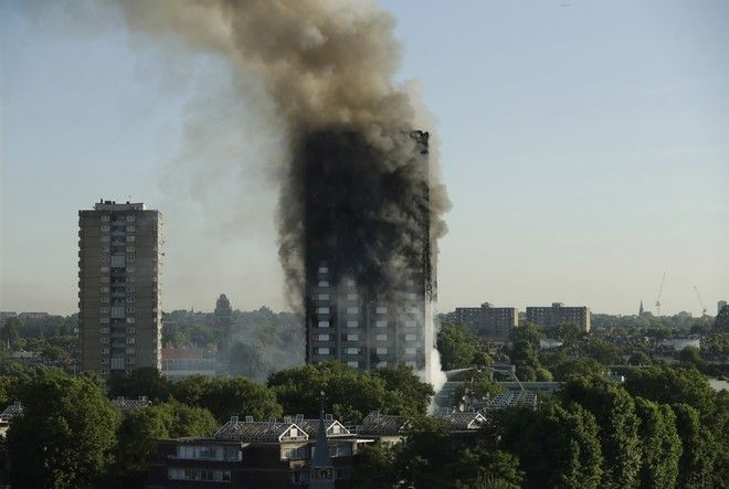 Smoke rises from a building on fire in London, Wednesday, June 14, 2017. A massive fire raced through the 27-story high-rise apartment building in west London early Wednesday, sending at least 30 people to hospitals, emergency officials said. (AP Photo/Matt Dunham)