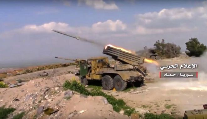 """In this Friday, March 31, 2017 frame grab from video provided by the government-controlled Syrian Central Military Media, Syrian army rocket launcher fires at insurgent groups position, in Hama, north Syria. Warplanes pounded rebel-held areas north of the Syrian city of Hama on Friday, as pro-government forces continued to reverse gains made by insurgent groups in the area. Arabic reads, """"Central Military Media, Hama, Syria."""" (Syrian Central Military Media, via AP)"""