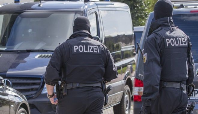 "Police walk in front of a house in Banzkow, eastern Germany, Monday, Aug. 28, 2017. German prosecutors say authorities have raided the homes and workplaces of two people who apparently opposed the country's policy on migrants and are suspected of drawing up a ""kill list"" of left-wingers.  (Jens Buettner/dpa via AP)"