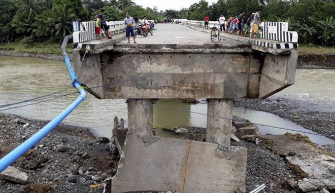 People gather on a bridge which was damaged by the onslaught of the flooding brought about by tropical storm Tembin, Sunday, Dec. 24, 2017 in Zamboanga Del Sur in southern Philippines. Tropical Storm Tembin unleashed flash floods that swept away people and houses and set off landslides in the southern Philippines. (AP Photo/Daisy Barimbao)
