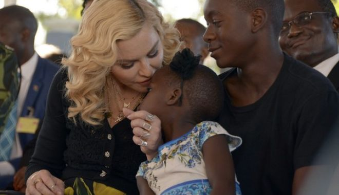 US musician Madonna, kisses one of her adopted daughters Stella, as son David Banda, right, looks on at the opening of The Mercy James Institute for Pediatric Surgery and Intensive Care, located at the Queen Elizabeth Central Hospital in the city of Blantyre, Malawi, Tuesday, July 11, 2017. Madonna was in Malawi on Tuesday for the official opening of a hospital children's wing funded by her charity and named after one of the four children the pop star has adopted from the impoverished southern African nation. (AP Photo Thoko Chikondi)