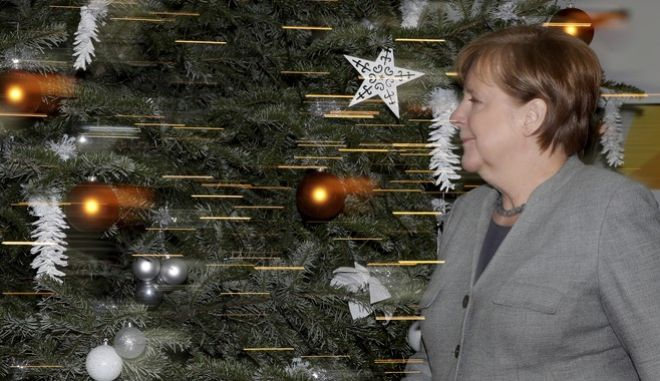In this photo taken with slow shutter speed German Chancellor and Chairwoman of the German Christian Democratic Party (CDU), Angela Merkel, arrives for a press conference after a party's board meeting in Berlin, Germany, Monday, Dec. 18, 2017. (AP Photo/Michael Sohn)