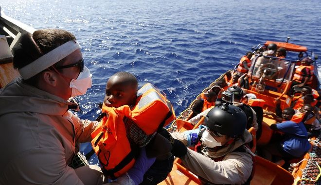 A child is helped to board on the Norwegian Siem Pilot ship during a migrant search and rescue mission off the Libyan Coasts, Tuesday, Sept. 1, 2015. Four dead bodies and hundreds of migrants were transferred on the Norwegian Siem Pilot ship from an Italian Navy ship and a Doctor Without Borders vessels after being rescued in different operation in the mediterranean sea. (AP Photo/Gregorio Borgia)