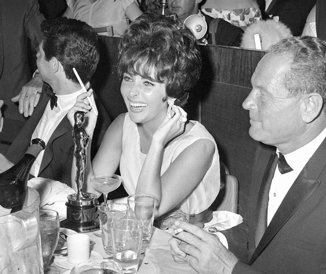Actress Elizabeth Taylor is seen April 18, 1961 as she celebrates winning her first Oscar at the Beverly Hills Hotel, accompanied by her husband Eddie Fisher, left.  The big supper party was thrown in honor of the Oscar winners and other Hollywood notables.  (AP Photo/David F. Smith)