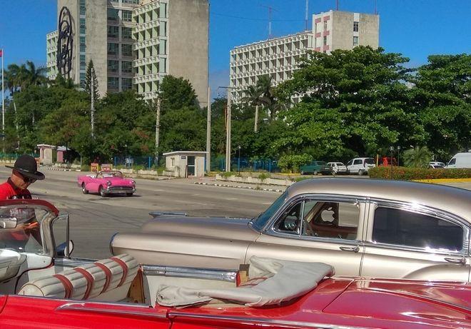 Αυτοκίνητα αντίκες που έχουν μετατραπεί σε ταξί περιμένουν τους τουρίστες στην πλατεία της Επανάστασης στην Αβάνα, υπό το βλέμμα του Τσε