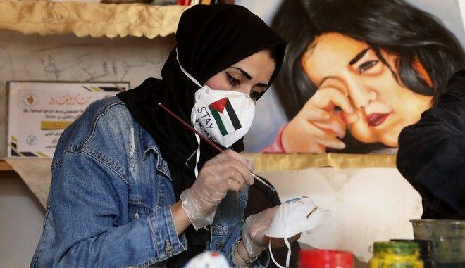 Γυναίκα από την Παλαιστίνη διακοσμεί μία προστατευτική μάσκα για τον κορονοϊό