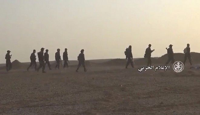 """This frame grab from video provided by the government-controlled Syrian Central Military Media and released Sunday, July 09, 2017, shows Syrian forces taking up positions during fighting between Government forces and Islamic State group militants, in the Palmyra desert, Homs provence, Syria. Arabic reads, """"Military Media."""" (Syrian Central Military Media, via AP)"""