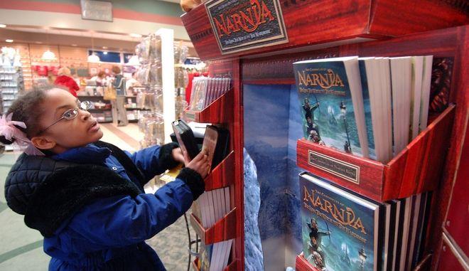 """Κορίτσι σε βιβλιοπωλείο κοιτά σε ράφια τα βιβλία της σειράς """"Τα Χρονικά της Νάρνια"""""""