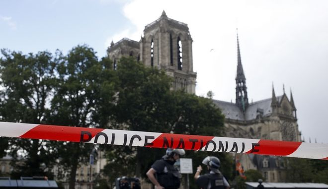 FILE- In this Tuesday, June 6, 2017 file photo, police officers seal off the access to Notre Dame cathedral in Paris, France. The chief prosecutor in Paris said Saturday, June 10 2017, that a hammer-wielding man who attacked police officers patrolling in front of Notre Dame Cathedral appears to have radicalized himself through the internet and was unknown to French police and intelligence services. (AP Photo/Matthieu Alexandre, File)