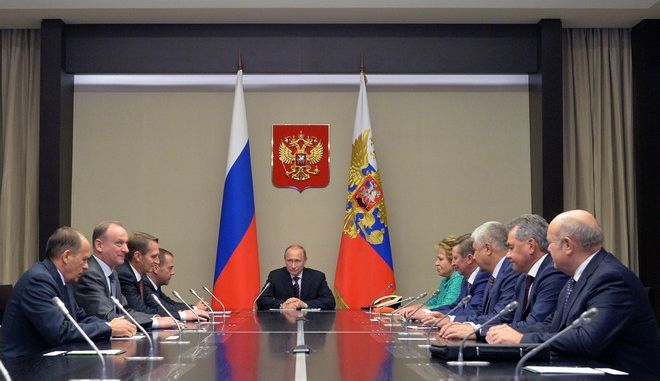 Russian President Vladimir Putin, center, listens as he meets with members of Russia's Security Consul in the Novo-Ogaryovo residence outside Novo-Ogaryovo, Russia, Tuesday, Sept. 29, 2015. (Alexei Druzhinin, RIA-Novosti,  Kremlin Pool Photo via AP)