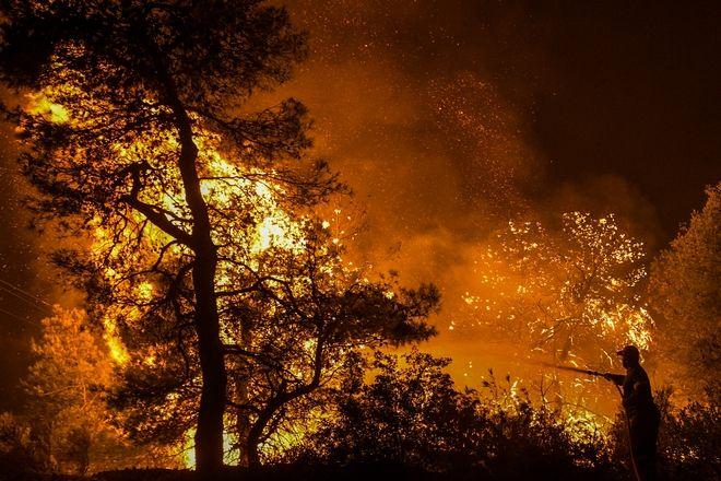 Πυροσβέστες προσπαθούν αργά το βράδυ να περιορίσουν την μεγάλη πυρκαγιά που κατακαίει από τις 3 τα χαράματα της Τρίτης 13 Αυγούστου 2019, την περιοχή Μεσσαπίων-Δίρφυος.