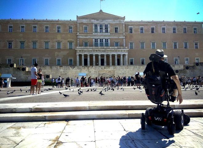 Άτομο με αναπηρία προσπαθεί να βρει τρόπο να πλησιάσει με το αμαξίδιο το μνημείο του Άγνωστου Στρατιώτη.
