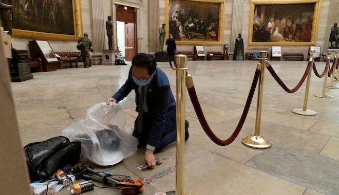 Ο βουλευτής Άντι Κιμ μαζεύει τα σκουπίδια που άφησαν οι εισβολείς στο Καπιτώλιο, 7 Ιανουαρίου 2021.