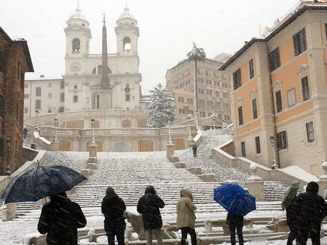 People look at the Spanish Steps during a snowfall, in Rome, Monday, Feb. 26, 2018. Romans have awoken to a rare snowfall, after an Arctic storm passing over much of Europe dumped enough snow to force schools to close and public transport to reduce services.  (AP Photo/Trisha Thomas)
