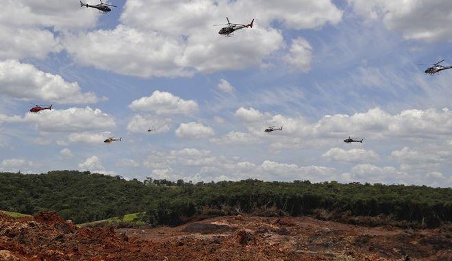 Ελικόπτερα πάνω από περιοχή που επλήγη από τον χείμαρρο λάσπης μετά την κατάρρευση του φράγματος