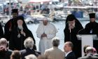 Pope Francis (C), the Ecumenical Patriarch Bartholomew I (L), spiritual leader of the worlds Orthodox Christians and Archbishop of Athens and All Greece eronyms II (R), head of the Church of Greece, observe a minute of silence for migration victims in the Aegean Sea, at the port of Mytilene, at the island of Lesvos, Greece on April 16, 2016. /    ,                      ,    , , 16  2016.
