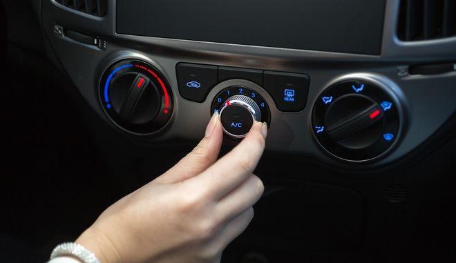 Γυναίκα ανάβει το κλιματιστικό αυτοκινήτου