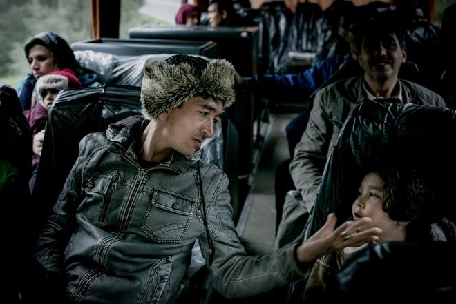 Mirza Hossain and his son, on a bus to a hotel, before boarding for Piraeus harbor. They had left Ghazni in Afghanistan two months before.