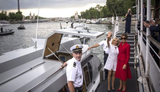 US First Lady Melania Trump, right, and French president's wife Brigitte Macron wave after a boat trip down the River Seine in Paris, Thursday, July 13, 2017. Donald Trump is in Paris for a high profile two-day visit during which US President will be the guest of honour of his French counterpart Emmanuel Macron at the annual Bastille Day parade. (AP Photo/Kamil Zihnioglu)