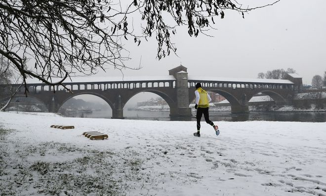 A man runs next the Ponte Coperto (Covered bridge), also known as Ponte Vecchio (Old Bridge), a brick and stone arch bridge over the Ticino River, during a snowfall in Pavia, some 40 kilometers (24 miles) south east of Milan, Italy, Thursday, March 1, 2018. Persistent snow and freezing conditions from a Siberian cold snap are causing delays in many parts of mainland Europe, with roads and train services hit particularly hard. (AP Photo/Antonio Calanni)