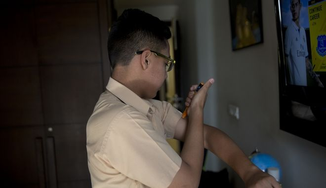 In this photo taken Wednesday, April 26, 2017, Rohin Sarin injects insulin into his arm at his house in New Delhi, India. Rohin is one of a growing number of Indians with diabetes, with the disease increasingly afflicting children and adolescents in the fast-growing South Asian country. Nearly 30 percent of Indias teenagers are obese, nearly twice the number in 2010, according to health ministry statistics. (AP Photo /Tsering Topgyal)