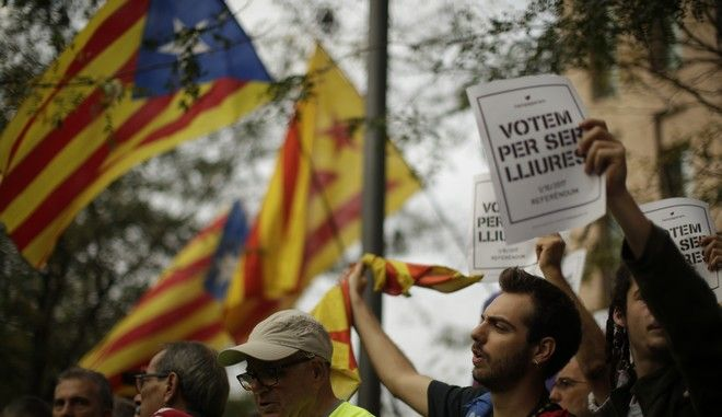 "Protesters gather in support of Catalan officials that were arrested at the courthouse in Barcelona, Spain, Friday, Sept. 22, 2017. A demonstration against police raids and arrests of officials as part of a crackdown on a planned Catalan independence referendum has ended after those arrested were released.  Banners reads in Catalan: ""We vote to be free"". (AP Photo/Manu Fernandez)"