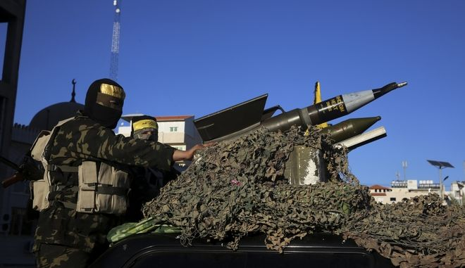 Masked Palestinian militants from Nidal Amodi Brigades, a military wing of Fatah movement linked to Palestinian President Mahmoud Abbas, sit behind rocket launcher on a vehicle in Gaza City, Saturday, Dec. 31, 2016. (AP Photo/Adel Hana)