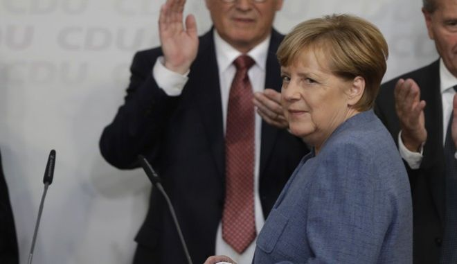 German Chancellor Angela Merkel appears on the stage at the headquarters of the Christian Democratic Union CDU in Berlin, Germany, Sunday, Sept. 24, 2017. (AP Photo/Michael Sohn)
