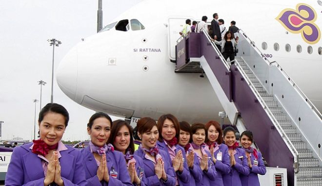"""Thai Airways crew members pose beside the first Airbus Thai A380-800, bestowed with the royal name of """"Si Rattana,"""" at Bangkok's Suvarnabhumi International Airport September 29, 2012. The plane is Thai Airways first out of six Airbus Thai A380-800 and it will begin operation on October 6, according to the airline's press release. The Airbus A380-800 is the largest passenger airplane in the world. REUTERS/Chaiwat Subprasom (THAILAND - Tags: TRANSPORT BUSINESS) - RTR38KGG"""