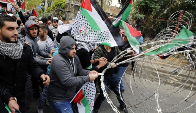 Protesters try to remove barbed wires that block a road leading to the U.S. embassy during a demonstration in Aukar, east of Beirut, Lebanon, Lebanon, Sunday, Dec. 10, 2017. A few hundred demonstrators, including Palestinians, pelted security outside the embassy with stones and burned an effigy of U.S. President Donald Trump in a protest to reject Washington's recognition of Jerusalem as capital of Israel. (AP Photo/Bilal Hussein)