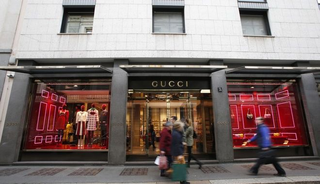 People walk in front of Gucci shop in Monte Napoleone street in Milan, Italy, Thursday, Oct. 20, 2016. The terror threat in Europe, a strong dollar and uncertainty over the U.S. presidential elections have eroded the confidence of the globe's big-spenders, holding luxury purchases flat in 2016, according to a study released Thursday. (AP Photo/Antonio Calanni)