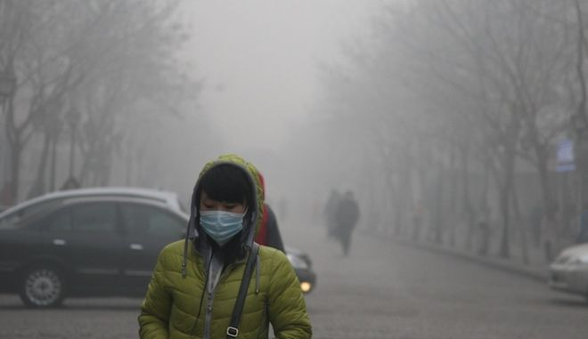 HARBIN, CHINA - DECEMBER 03:  (CHINA OUT) A pedestrian wearing a mask walks along a road as heavy smog engulfs the city on December 3, 2013 in Harbin, China. Harbin Meteorological Bureau issued an orange warning on smog on Tuesday morning.  (Photo by ChinaFotoPress/ChinaFotoPress via Getty Images)