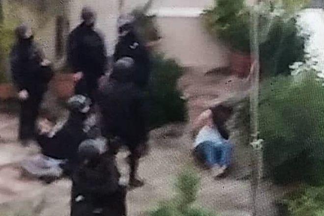 Η στιγμή που αστυνομικοί ακινητοποιούν τους ιδιοκτήτες του οικήματος, δίπλα από το υπό κατάληψη κτίριο