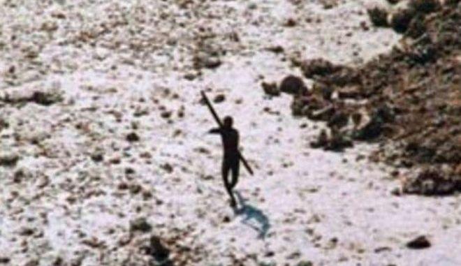 Μέλος της πρωτόγονης φυλής φωτογραφημένο το 2004 να ρίχνει βέλη σε ελικόπτερο