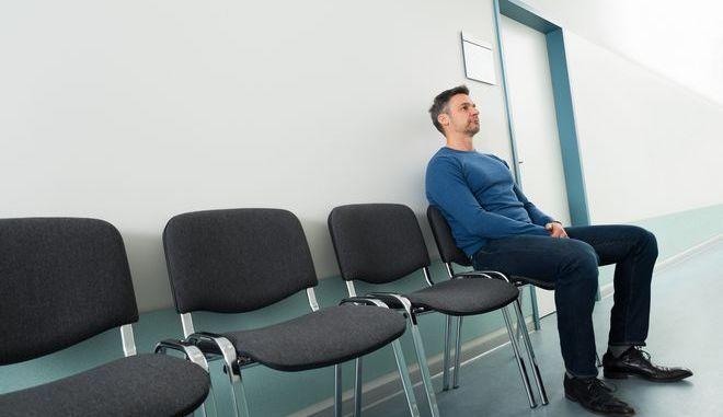 Άνδρας κάθεται σε καρέκλα νοσοκομείου