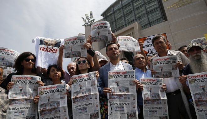 """Journalists and activists gather outside the court in Istanbul, Friday, July 28, 2017, protesting against the trial of journalists and staff from the Cumhuriyet newspaper, staunchly opposed to President Recep Tayyip Erdogan, accused of aiding terror organisations. The court was expected to decide whether the suspects should be released from jail pending the trial's outcome. The headlines read: """" Freedom."""" (AP Photo/Emrah Gurel)"""