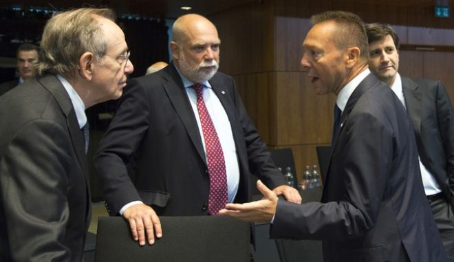 Governor of the Central Bank of Greece Yannis Stournaras, right, speaks with Italian Finance Minister Pier Carlo Padoan, left, during a meeting of EU finance ministers at the European Council building in Luxembourg on Saturday, Sept. 12, 2015. European Union finance ministers and central bankers hold informal talks to discuss taxation and ways to further deepen cooperation on the EU¢s euro single currency. (AP Photo/Virginia Mayo)