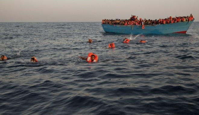 Migrants, most of them from Eritrea, jump into the water from a crowded wooden boat as they are helped by members of an NGO during a rescue operation on the Mediterranean sea, about 13 miles north of Sabratha, Libya, Monday, Aug. 29, 2016. Thousands of migrants and refugees were rescued Monday morning from more than 20 boats by members of Proactiva Open Arms NGO before transferring them to the Italian cost guards and others NGO vessels operating at the zone. (AP Photo/Emilio Morenatti)
