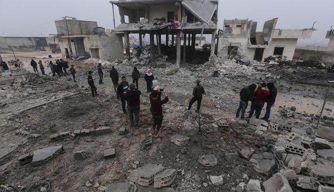 Άνθρωποι κοιτάζουν την καταστροφή σπιτιών στην πόλη της Αλ-Ιανάχ, δυτικά του Χαλεπίου, Συρία