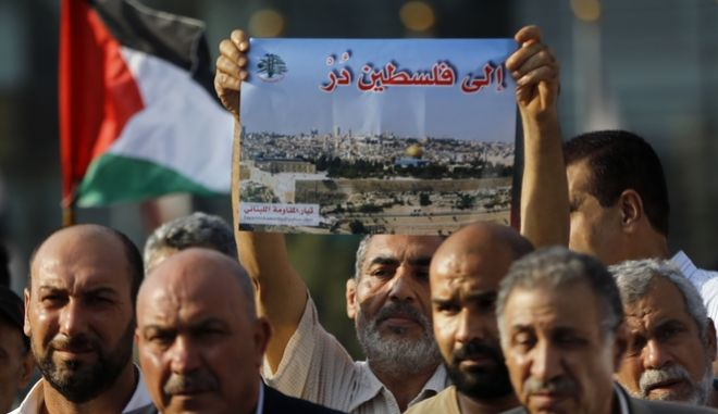 "A Palestinian man living in Lebanon holds a placard with Arabic reading, ""turn toward Palestine,"" during a sit-in in support of Palestinians and the Jerusalem holy site of the Al Aqsa Mosque, in front of the United Nations Headquarters in Beirut, Lebanon, Thursday, July 20, 2017. (AP Photo/Bilal Hussein)"