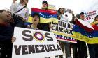 Manifestantes opuestos al gobierno venezolano cantan afuera de la Organización de Estados Americanos (OEA) durante la sesión extraordinaria del Consejo Permanente, en Washington, el lunes 3 de abril de 2017. (AP Foto/José Luis Magana)