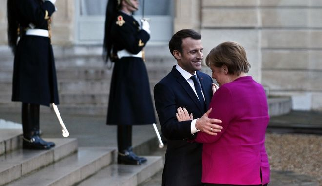 France's President Emmanuel Macron, left, welcomes German Chancellor Angela Merkel, prior to a meeting, at the Elysee Palace, in Paris, Friday, Jan. 19, 2018. (AP Photo/Thibault Camus)