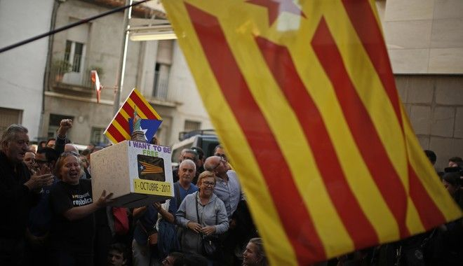 A protester holds a fake ballot box as they block a street next to private postal service company Unipost during a protest against a search for propaganda supporting Catalonia's independence referendum in Terrassa, Spain, Tuesday, Sept. 19, 2017. The Spanish government has vowed to stop the planned Oct. 1 vote that it calls illegal. But Catalonia's leaders have pushed ahead even after Spain's Constitutional Court suspended the law passed by Catalonia's regional parliament that convoked the referendum. (AP Photo/Manu Fernandez)